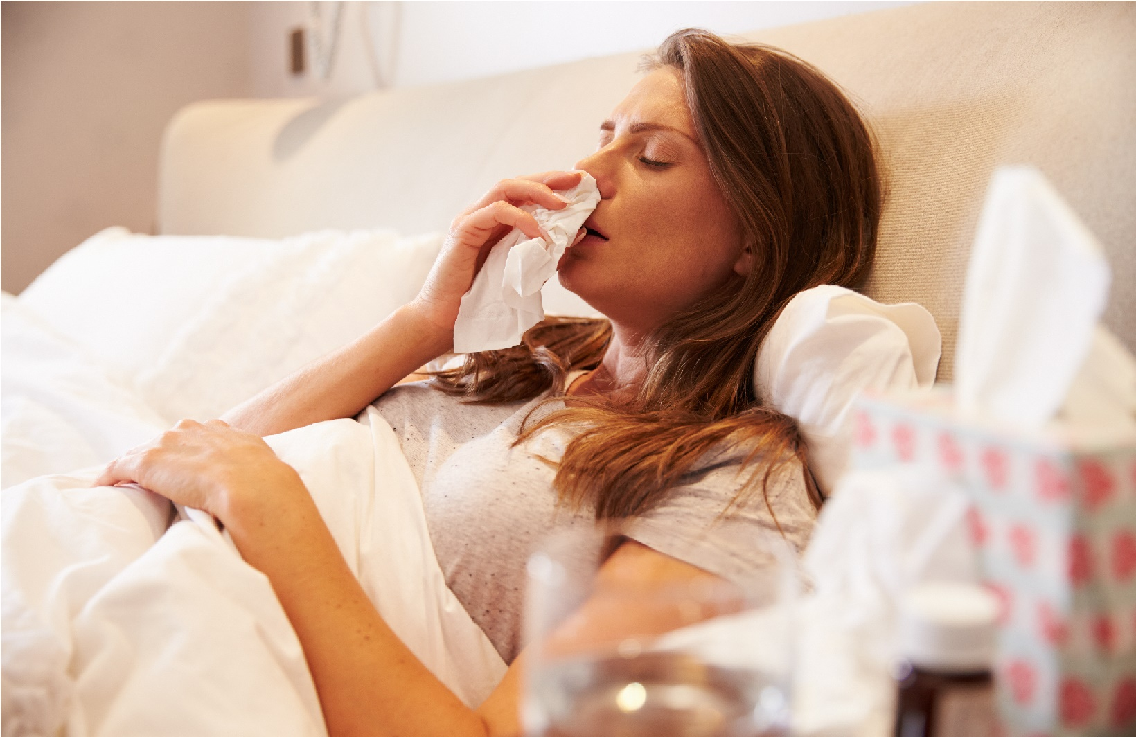 Woman Suffering From Cold and Flu Symptoms Lying In Bed With Tissue