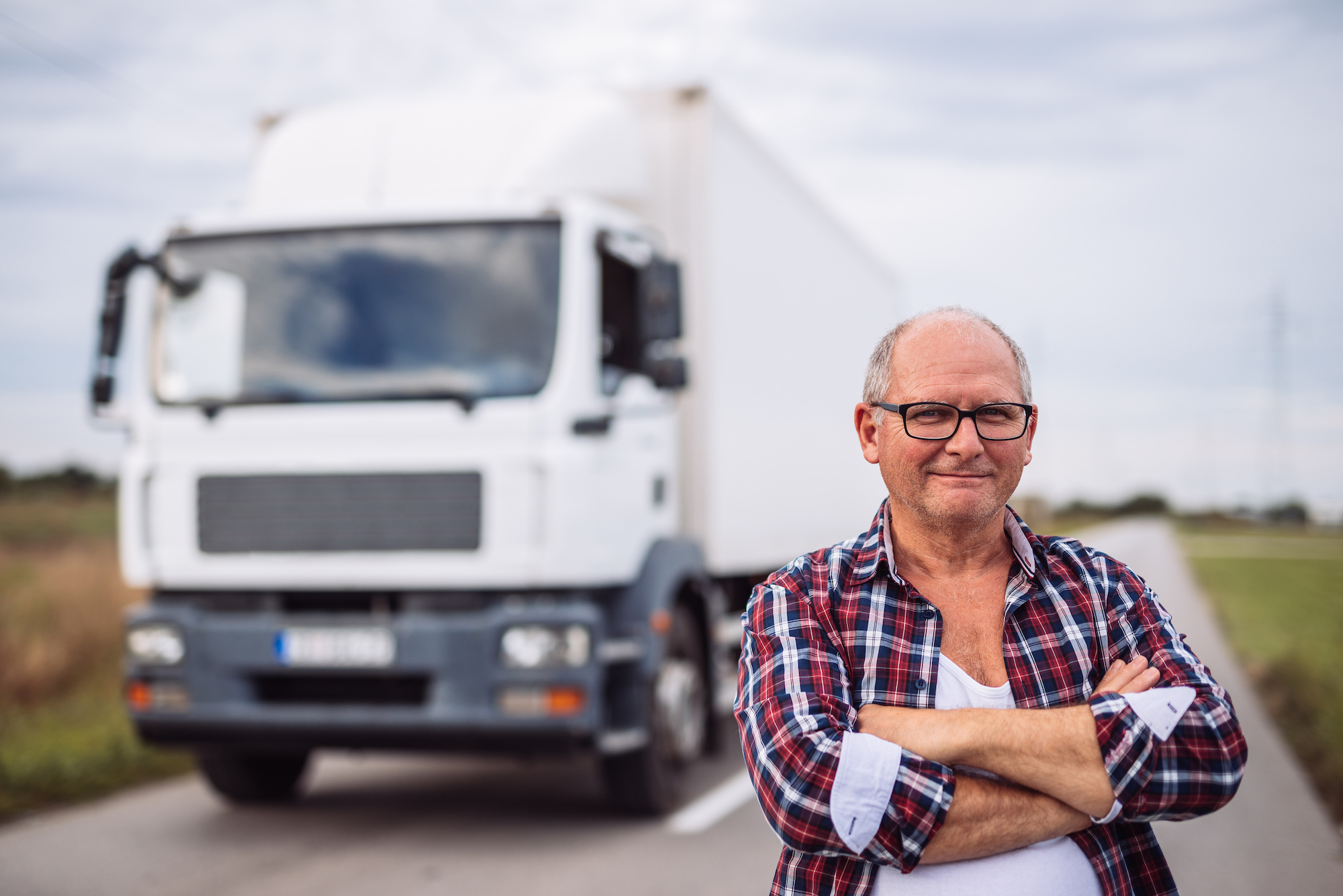 truck driver happy next to truck after passing DOT physical