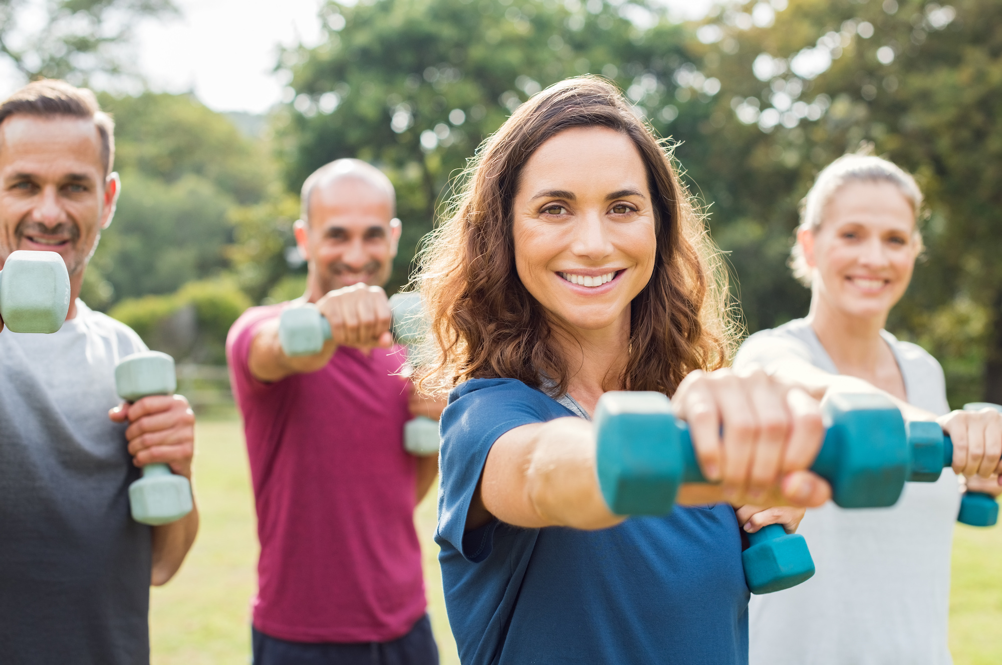 employer wellness services - Mature people in training session of aerobics using dumbbells at park